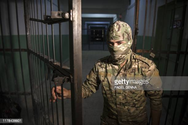 Fighter with the Syrian Democratic Forces stands guard in a prison where men accused of being affiliated with the Islamic State group are kept in the...
