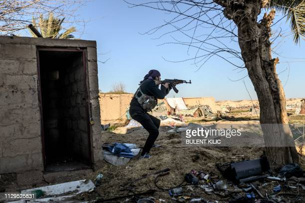 Fighter with the Syrian Democratic Forces takes aim with his Kalashnikov assault rifle after seeing a man walking towards his position in the town of...