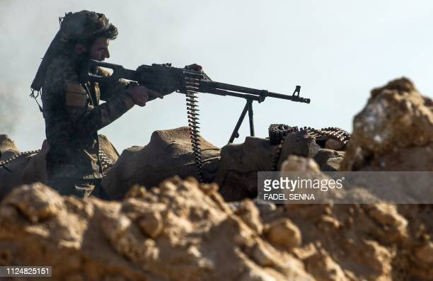Fighter with the US-backed Syrian Democratic Forces aims his weapon during an operation to expel Islamic State group jihadists from the Baghouz area...