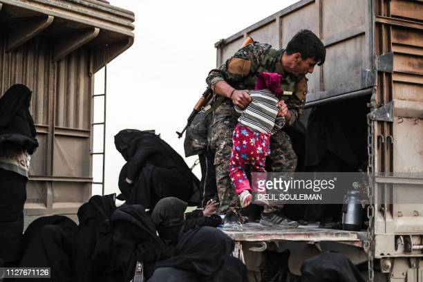 TOPSHOT A fighter with the USbacked Syrian Democratic Forces help civilians at a screening area for those who are evacuated from the Islamic State...