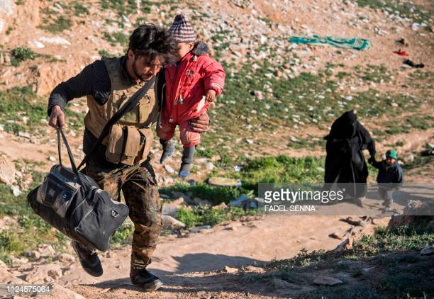 A fighter with the USbacked Syrian Democratic Forces helps women and their children on a field after they fled from the Baghouz area in the eastern...