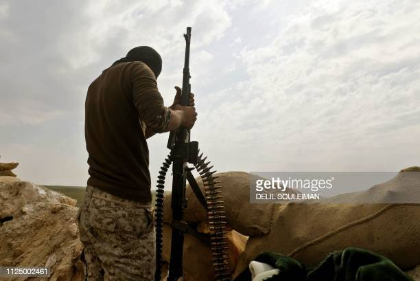 Fighter with the US-backed Syrian Democratic Forces holds his weapon during an operation to expel Islamic State group jihadists from the Baghouz area...