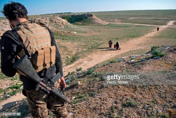 A fighter with the USbacked Syrian Democratic Forces keeps watch as civilians flee from the Baghouz area in the eastern Syrian province of Deir Ezzor...