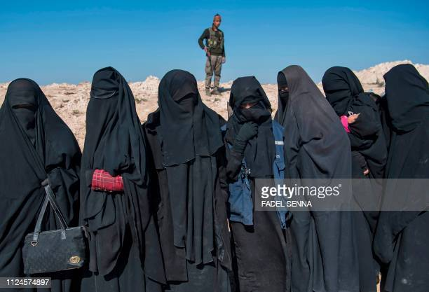TOPSHOT A fighter with the USbacked Syrian Democratic Forces keeps watch near veiled women standing on a field after they fled from the Baghouz area...
