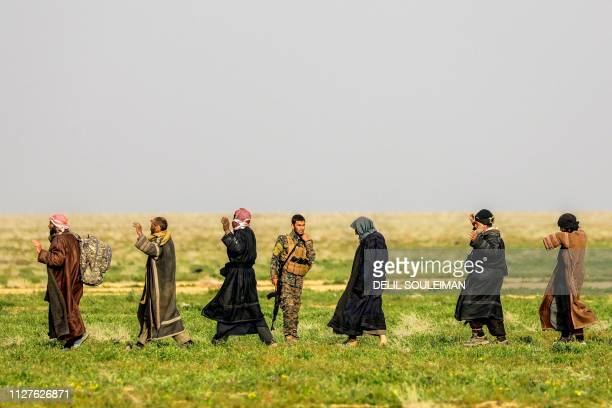 TOPSHOT A fighter with the USbacked Syrian Democratic Forces stands guard as people queue at a scanning area for those who are evacuated from the...