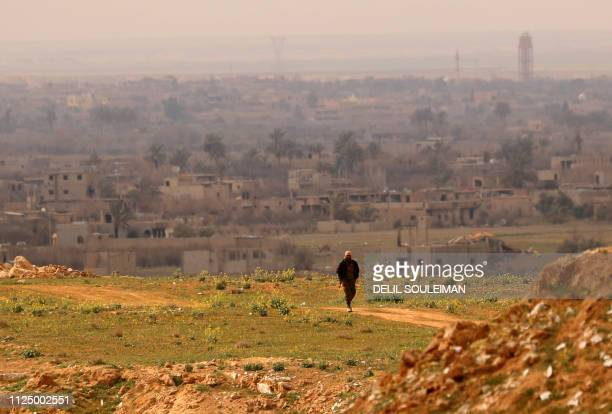 Fighter with the US-backed Syrian Democratic Forces walks at a position in the Baghouz area in the eastern Syrian province of Deir Ezzor on February...