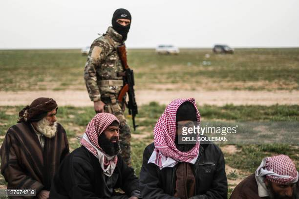 TOPSHOT A fighter with the USbacked Syrian Democratic Forces walks past men at a screening area for those who are evacuated from the Islamic State...