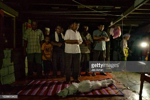 Fighters and family members offer prayers to the body of Jahira Ibrahim Makmud after drowning from a fishpond near their makeshift house on August 26...