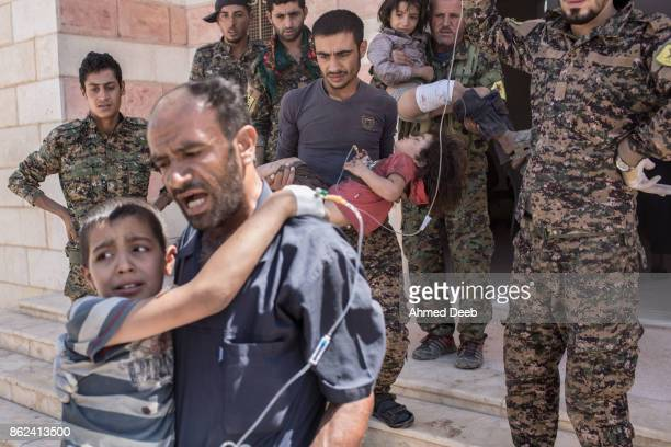 Fighters carry children who were injured by a mine which exploded when a group of civilians were escaping the Islamic State controlled areas of Raqqa...