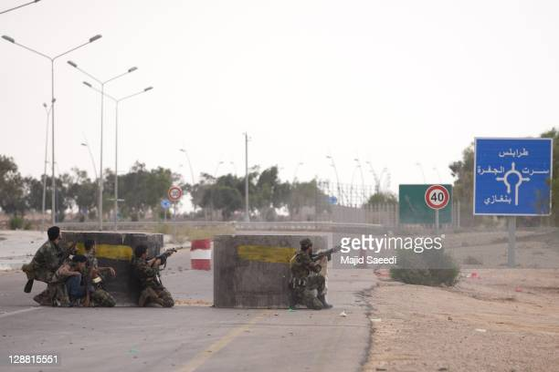 Fighters fire from cover on October 7, 2011 in Sirte, Libya. National Transitional Council fighters say this is the final assault on Muammar...