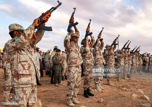 """Fighters fire salutatory rounds in the air during the funeral of General Wanis Bukhamada, commander of the """"Saiqa"""" of the self-proclaimed Libyan..."""