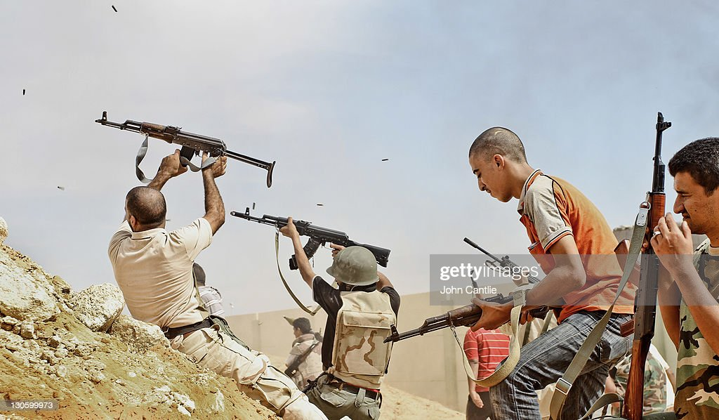 NTC fighters fire their weapons wildly from behind a sand bank in the Dollar Complex of Colonel Gaddafi's home city of Sirte on October 10, 2011 in Libya. NTC forces are continuing their advance on Colonel Muammar Gaddafi's hometown of Sirte.