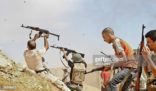 NTC fighters fire their weapons wildly from behind a sand bank in the Dollar Complex of Colonel Gaddafi's home city of Sirte on October 10 2011 in...