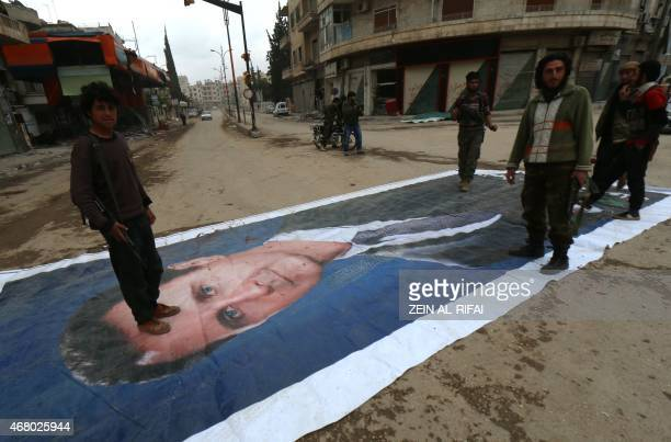 Fighters from a coalition of Islamist forces stand on a huge portrait of Syrian President Bashar alAssad on March 29 in the Syrian city of Idlib the...