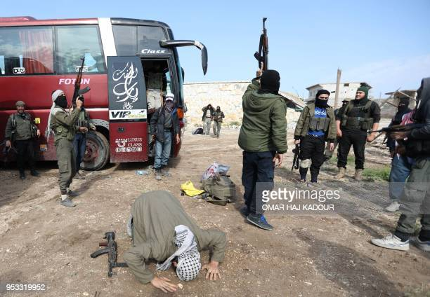 Fighters from Hayat Tahrir alSham and members of their families arrive in a rebelheld area of the AlEis crossing in Syria's northern Aleppo province...