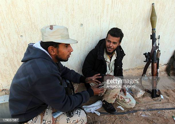 Fighters from Libya's new regime chat after heavy fighting in the center of the town of Sirte the hometown of the former Libyan leader on October 11...
