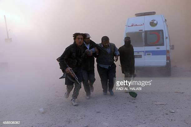 Fighters from the alQaida group in the Levant AlNusra Front help a wounded man following a reported barrel bomb attack by government forces in the...