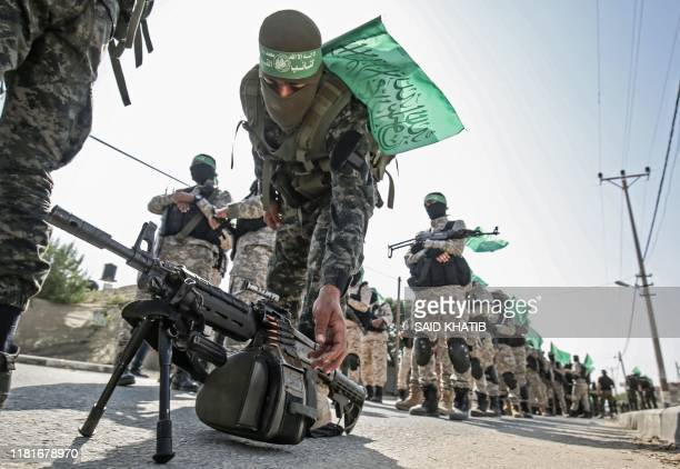 Fighters from the EzzAl Din AlQassam Brigades the armed wing of the Hamas movement holding automatic rifles take part in an antiIsrael military show...