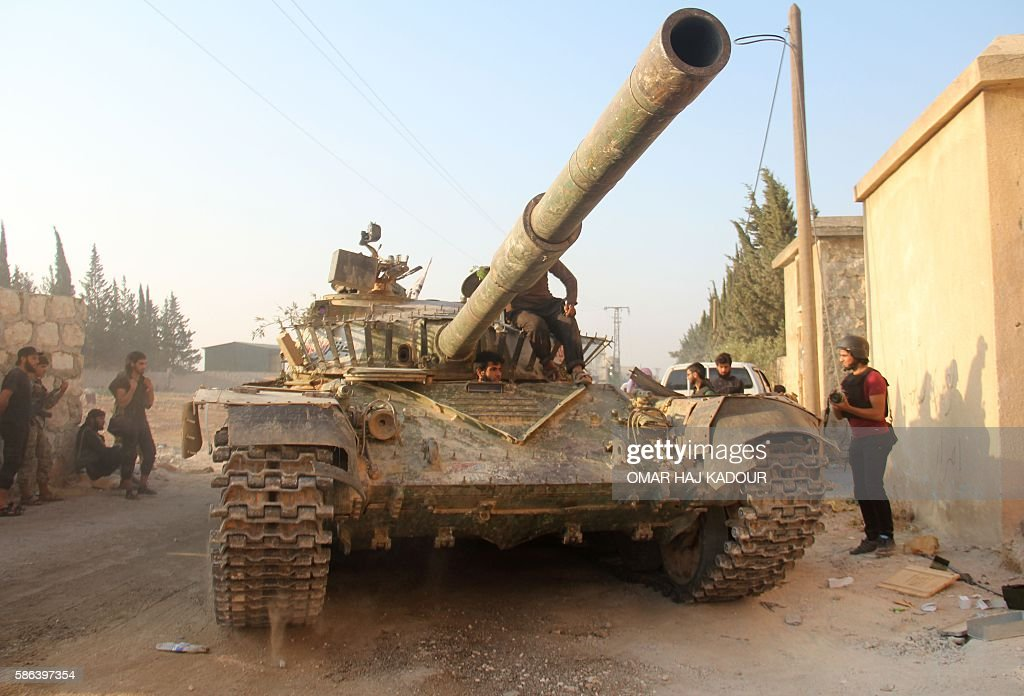 Fighters from the former Al-Nusra Front -- renamed Fateh al-Sham Front after breaking from Al-Qaeda -- drive a tank as they seized key positions south of Aleppo on August 6, 2016 in a major offensive to break the government siege of the city, the Syrian Observatory for Human Rights said. Fateh al-Sham Front announced having captured two military academies and a third military position. / AFP / Omar haj kadour