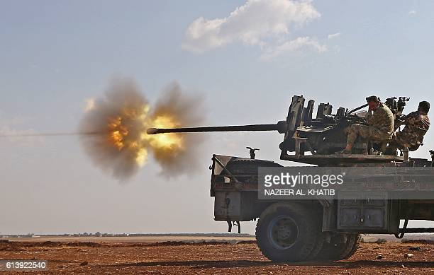Fighters from the Free Syrian Army fire an antiaircraft machine gun mounted on a vehicle deploy during fighting against the Islamic State group...