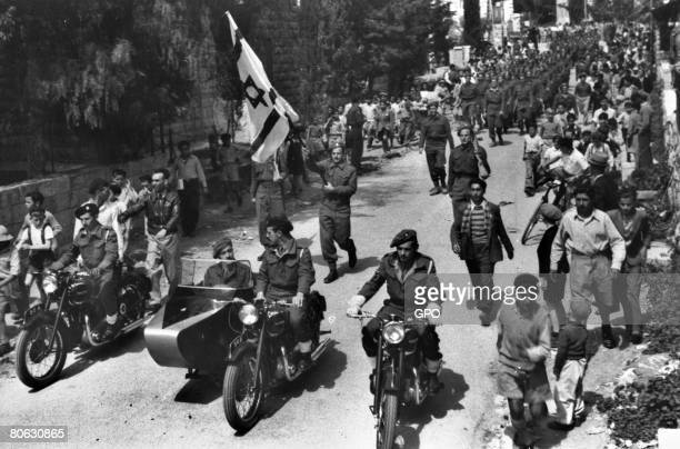 Fighters from the Haganah the Jewish underground parade with what would soon be the Israeli flag April 1 through the streets of Jewish Jerusalem in...