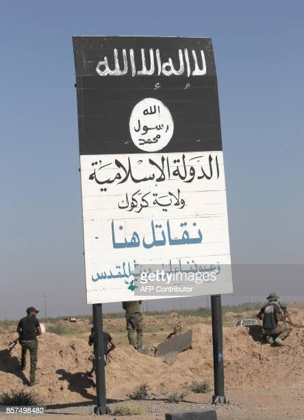 Fighters from the Hashed alShaabi backing Iraqi forces stand next to a billboard bearing the logo of the Islamic State group as they advance towards...