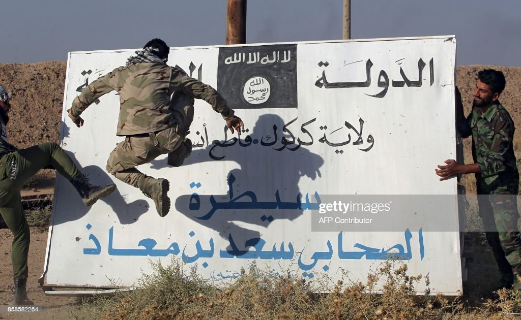 Fighters from the Hashed al-Shaabi (Popular Mobilisation units), backing the Iraqi forces, kick a billboard bearing the logo of the Islamic State (IS) group in Hawija on October 6, 2017, a day after the troops retook the northern city from Islamic State (IS) group fighters. /