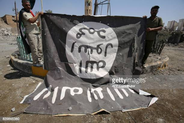Fighters from the Hashed alShaabi backing the Iraqi forces pose for a photograph with a flag of the Islamic State group in Tal Afar's Qalea central...