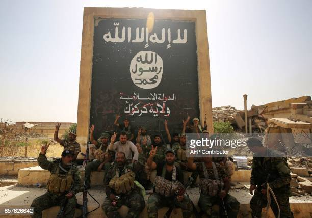 Fighters from the Hashed alShaabi backing the Iraqi forces pose in front of a mural depicting the emblem of the Islamic State group as troops advance...