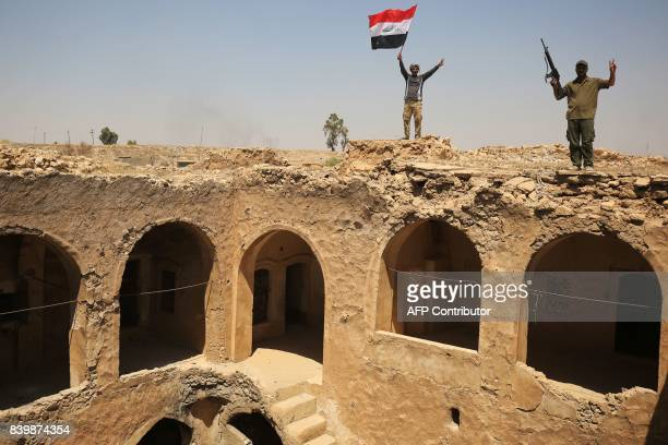 TOPSHOT Fighters from the Hashed alShaabi backing the Iraqi forces pose with the Iraqi flag from Tal Afar's Ottomanera historic citadel after troops...