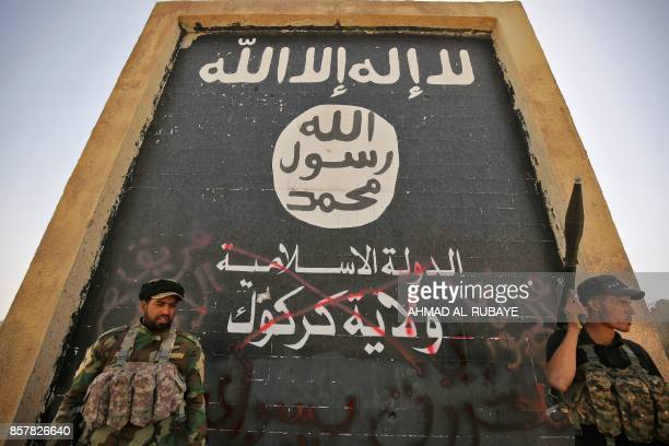 Fighters from the Hashed alShaabi backing the Iraqi forces stand in front of a mural depicting the emblem of the Islamic State group as troops...