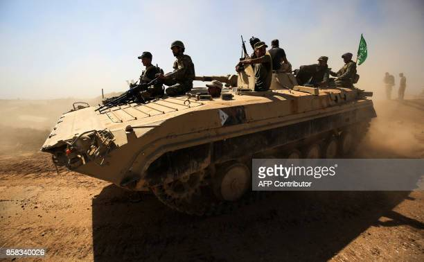 Fighters from the Hashed al-Shaabi paramilitaries ride atop an infantry-fighting vehicle as they advance towards villages between the northern Iraqi...