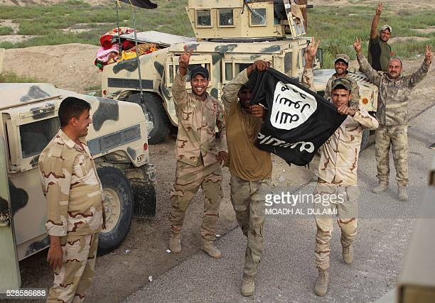 Fighters from the Iraqi progovernment forces hold up an Islamic State group flag and flash the Vsign during a military operation against IS near...