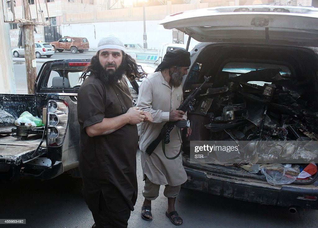 Fighters from the Islamic State group load a van with parts that they said was a US drone that crashed into a communications tower in Raqqa early on September 23, 2014. A US-led coalition on carried out its first air strikes and missile attacks against jihadist positions in Syria, with Damascus saying it had been informed by Washington before the operation began.