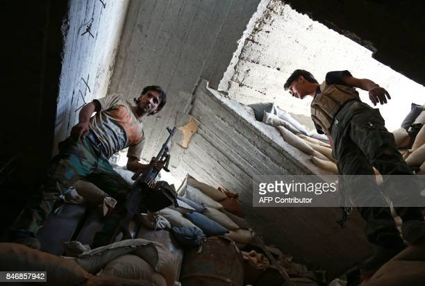 TOPSHOT Fighters from the Islamist rebel faction alRahman Corps guard a look out point on the frontline in Ain Tarma in the Eastern Ghouta area a...