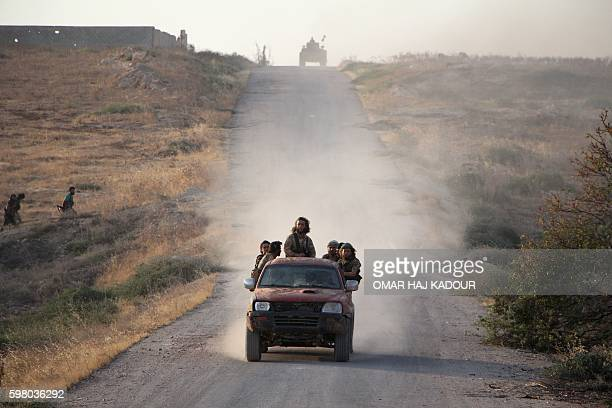 Fighters from the Jund alAqsa Islamist Brigade drive towards the northern Syrian town of Tayyibat alImam northwest of Hama on August 31 after taking...