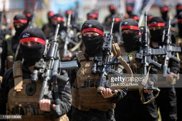 Fighters from the Kurdish Women's Protection units participate in a military parade on March 27 celebrating the total elimination of the Islamic...