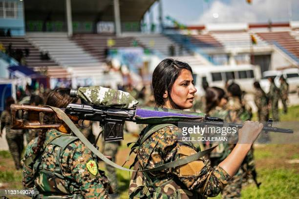 TOPSHOT Fighters from the Kurdish Women's Protection units participate in a military parade on March 27 celebrating the total elimination of the...