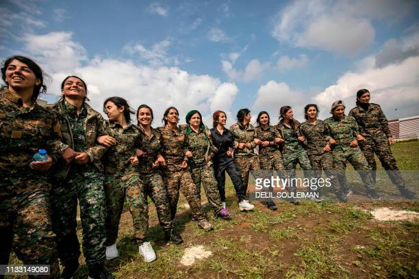 Fighters from the Kurdish Women's Protection units perform a traditional dance as they participate in a military parade on March 27 celebrating the...