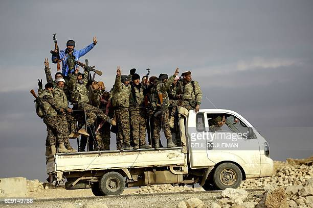 TOPSHOT Fighters from the KurdishArab alliance known as the Syrian Democratic Forces wave from a truck driving through the village of AlHaymar...
