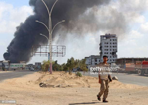 TOPSHOT A fighters from the separatist Southern Transitional Council walks with smoke billowing in the background in the government's de facto...