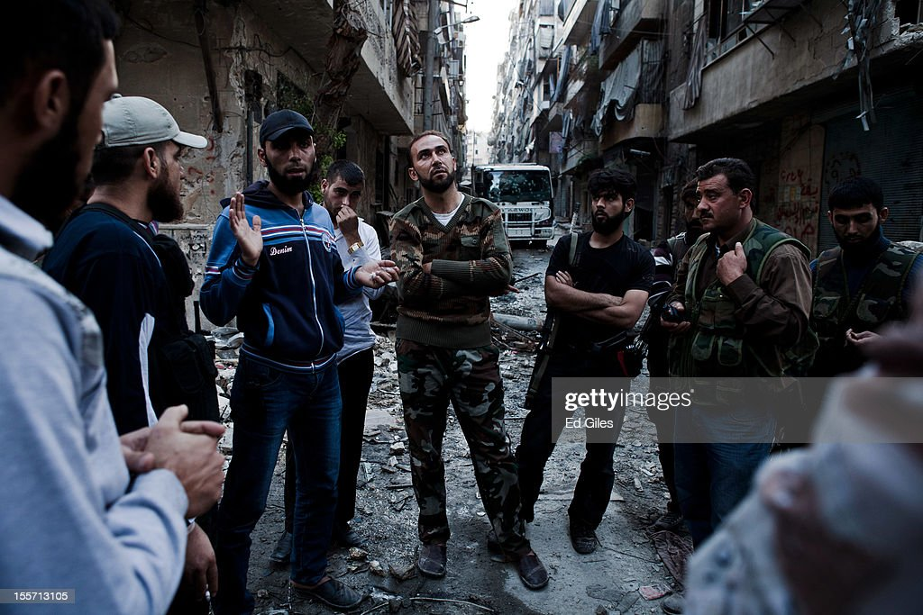 Fighters from the Shohada al Haq brigade of the Free Syrian Army meet with fighters from bridages based nearby to discuss tactics in the Salahudeen district on November 2, 2012 in Aleppo, Syria. The Shohada al Haq, or 'Martyrs of Truth' brigade control an area on the edge of the Salahudeen district in Aleppo, Syria's largest city. The brigade is made up of around 70 men, holding a handful of positions hidden in apartment blocks on the front line of Aleppo, facing toward Syrian army positions sometimes less than one hundred meters away. The Shohada al Haq use snipers to target Syrian regime troops as they move on the other side of the front, as well as moving between apartment blocks in the 'no man's land' between the two forces, occupying positions of advantage over the Syrian military. The brigade, or 'Katiba', live in the apartments they occupy, and the unit of rebel fighters is made up of former soldiers who defected from the Syrian military alongside men from Aleppo and other cities across Syria who have chosen to fight in Syria's increasingly violent civil war. (Photo by Ed Giles/Getty Images).
