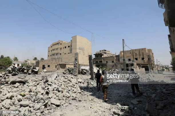 Fighters from the Syrian Democratic Forces a USbacked KurdishArab alliance walk through the rubble in an eastern area of the embattled city of Raqa...