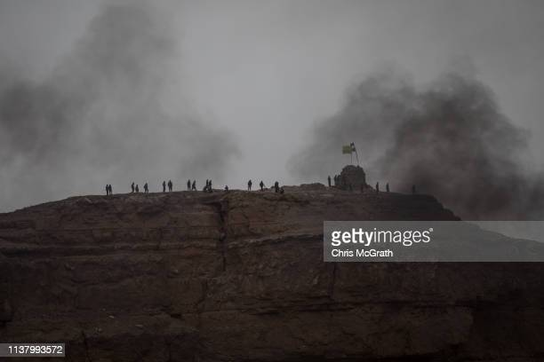 Fighters from the Syrian Democratic Forces are seen on a ridge line position overlooking the final ISIL encampment on March 24, 2019 in Baghouz,...