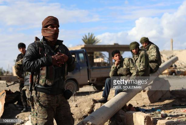 Fighters from the Syrian Democratic Forces gather in the front line village of Baghouz in the countryside of the eastern Syrian Deir Ezzor province...