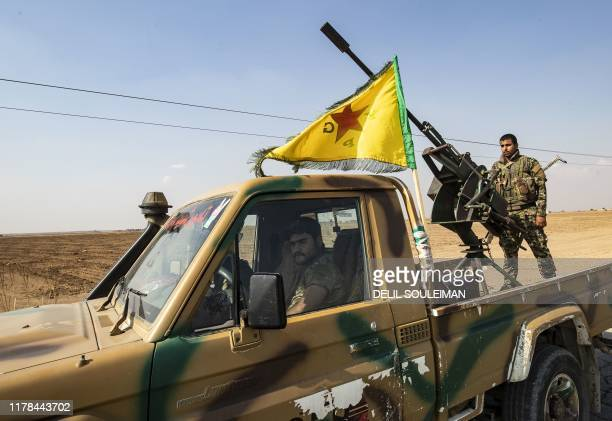Fighters from the Syrian Democratic Forces prepare to withdraw from the Sanjak Saadoun border area near the northern Syrian town of Amuda, on October...