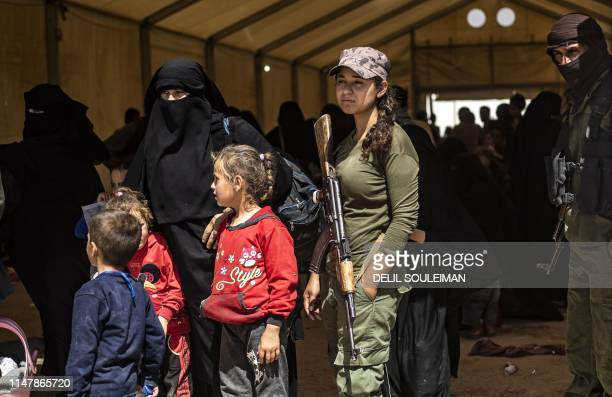 Fighters from the Syrian Democratic Forces stand guard as displaced people prepare to board a bus waiting outside the Al-Hol camp in northeastern...