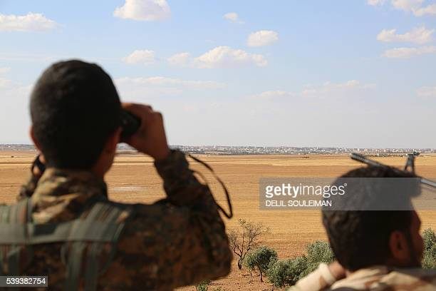 Fighters from the Syrian Democratic Forces use binoculars from a view point overlooking the northern Syrian town of Manbij held by the Islamic State...