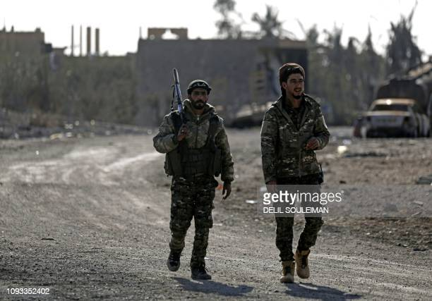 Fighters from the Syrian Democratic Forces walk in the front line village of Baghouz in the countryside of the eastern Syrian Deir Ezzor province on...