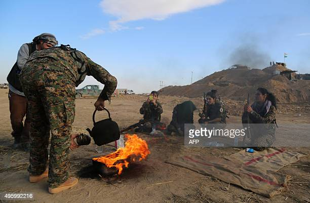 Fighters from the Syrian Democratic Forces which includes Kurds Arabs and Syriac Christians drink tea in countryside of the northeastern town of...